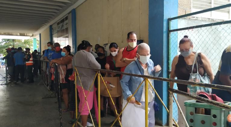 Agentes del orden público (al fondo), contribuyeron a organizar la cola en la panadería El Progreso, de la zona #16 de Alamar. Fotos: del autor